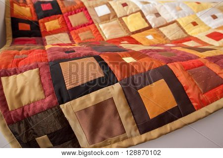 Patchwork quilt. Part of patchwork quilt as background. Klimt print. Color blanket. Orange quilt. Handmade.