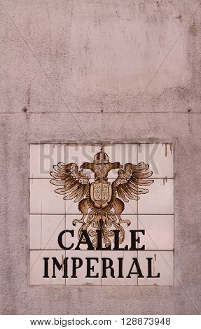 MADRID, SPAIN - MARCH 14, 2016: Closeup of the street sign in Madrid. They are hand-painted ceramic tiles typically composed within 9 or 12 tiles. They depict the name of the alley or street as well as illustrations that indicate special meanings. ** Not