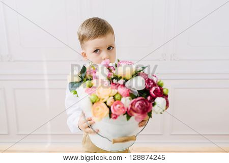 Boy holding a bucket of flowers on a white background in studio ** Note: Shallow depth of field