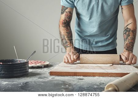 Tattooed Chief Man Cooks Pelmeni Or Dumplings Or Ravioli In Special Mold. Flatten Dough With Wooden