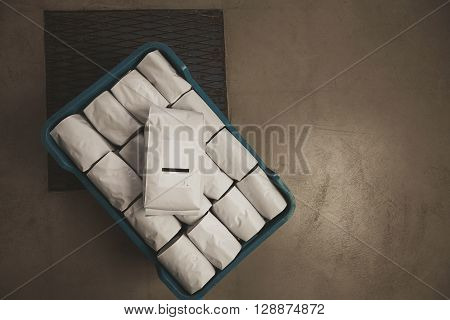 Top View White Filled With Coffee Or Tea Kg Sealed Packages In Plastic Box On Concrete Floor In Ware