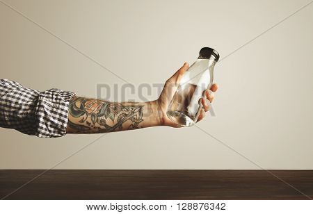 Brutal tattooed hand in folded plaid shirt holds glass transparent bottle with clean drinking water above red wooden table isolated on white