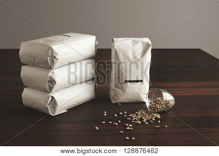 Big Hermetic Package With Blank Label Presented Near Other Four Lying Pouches Filled With Roasted Co