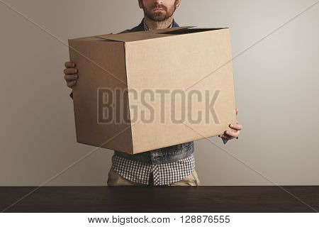 Bearded Brutal Courier In Jeans Work Jacket Holds Big Carton Paper Box With Goods Above Wooden Table