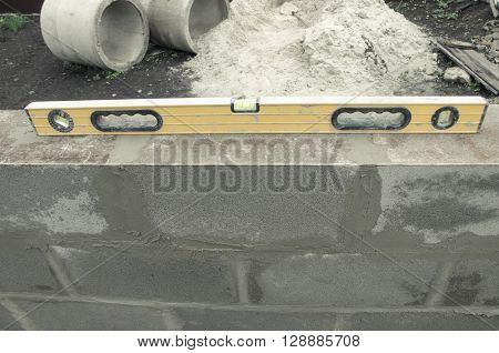 new beautyfull yellow level for building on the cinderblocks background. Process of building. to measure level of surface