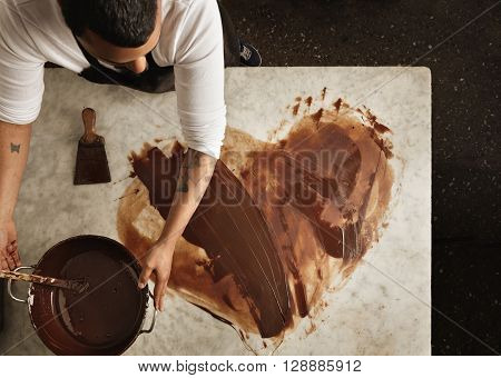Top View Professional Black Baker Uses Hot Chocolate To Draw A Lovely Heart, Before Makint Sweet Org