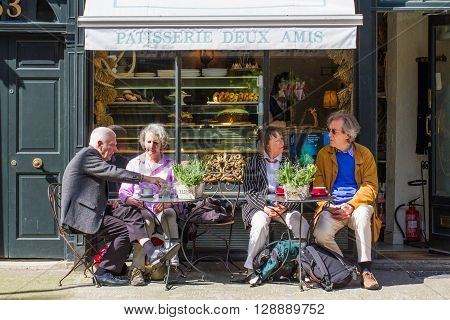 KINGS CROSS, LONDON, UK - MAY 5, 2016. Two elderly couples taking a break from sightseeing and sitting at the outdoor tables of a small French cafe on the streets of London.