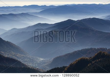 Carpathians mountain range in autumn fog over the forest.