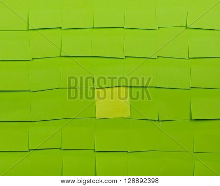 Background of green sticky notes. Yellow sticky note is among green sticky notes.