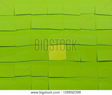 Background of green sticky notes. Yellow sticky note is among green sticky notes.