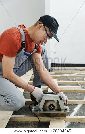 Worker cuts wooden floorboards using a circular saw.