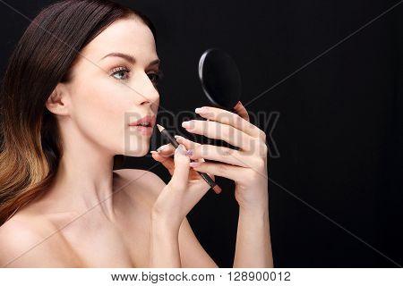 Woman performs makeup, paints lips liner pencil