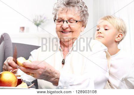 Grandmother to grandchild picks an apple peel