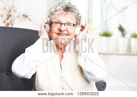 A moment of relaxation, rest grandmother listening to music.