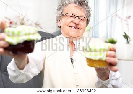 Mature woman with personally prepared jars of jams.