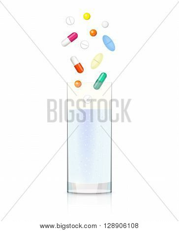 Glass with clear liquid and different pills and capsules