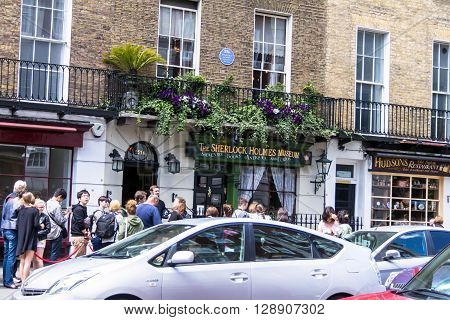 LONDON UK - JUNE 6 2015:Intensive traffic on Baker Street on background of  facade of the Sherlock Holmes house and museum in 221b Baker Street. Here is where Arthur Conan Doyle located the studio of the famous detective.
