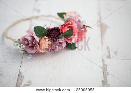 Handmade wraith or tiara made of pink and red rose flowers lying on bright white wooden background. Shallow depth of field macro close up copy space on the bottom