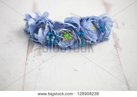 Diadem Of Blue Flowers On White Wooden Surface