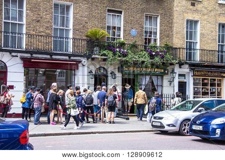 LONDON UK - JUNE 6 2015: Unidentified tourists near facade of the Sherlock Holmes house and museum in 221b Baker Street. Here is where Arthur Conan Doyle located the studio of the famous detective.