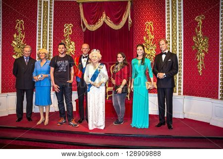 LONDON UK - JUNE 7 2015: Unidentified visitors are photographed for memory with the British royal family wax figures at Madame Tussauds Wax Museum.