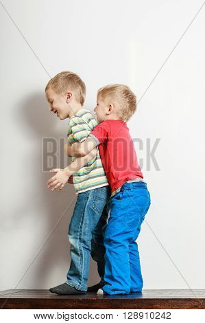 Free time fun and independence. Little boys play together hug hold brother indoors. Blonde children wear colorful clothes.