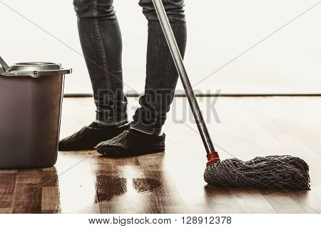 Closeup of human cleaning mopping floor. Person with mop and bucket at home. House cleanup.