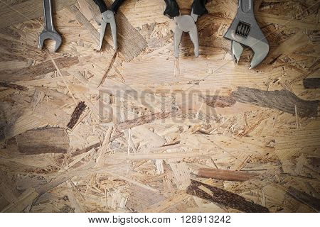 The working tools for construction and repair of house: wrench, pliers, spanner. Photo with copy space and vignetting effect.