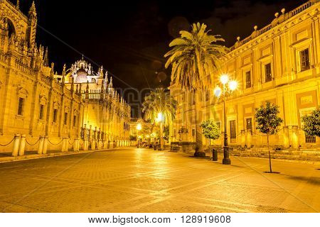 The Cathedral of Seville illuminated by night, with street and historic buildings around, the world's largest Gothic Cathedral and the third religious building to size, Andalucia, Spain.