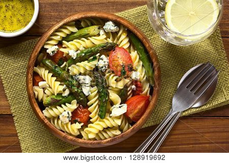 Baked green asparagus cherry tomato blue cheese and rotini pasta salad served in wooden bowl photographed overhead on dark wood with natural light