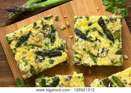 Frittata made of eggs green asparagus pea blue cheese parsley and brown rice photographed overhead on wooden board with natural light poster