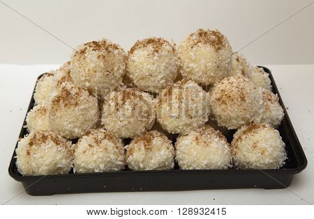 Sweet coconut spheres strewed by ground coffee