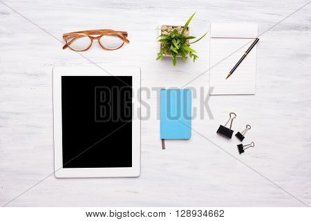 Top View Of Tablet Computer And Office Items On Wooden Table.