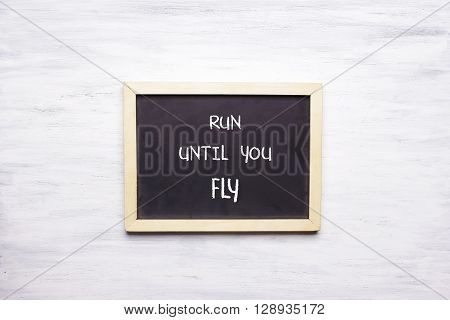 Top View Of Chalkboard With Run Until You Fly Written On It