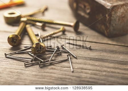 cross head bolt screws thread with nails and hammer on wooden desk closeup with copy space
