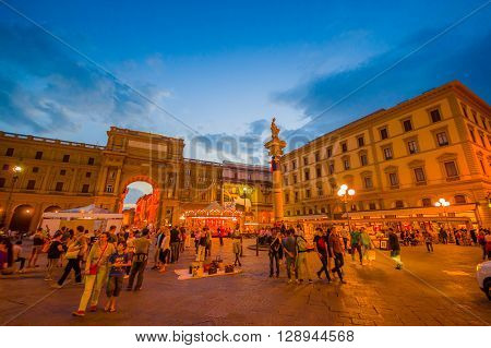FLORENCE, ITALY - JUNE 12, 2015: Republic Square in the center of Florence, beautiful at night with ilumination. Turists walking around and shopping.