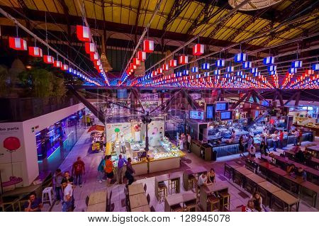 FLORENCE, ITALY - JUNE 12, 2015: Florence market iluminated, nice view of roof and decoration. People eating and visiting, pinturesque place.