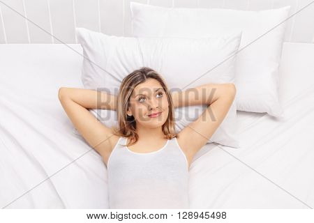 Carefree young woman laying on a comfortable bed and daydreaming