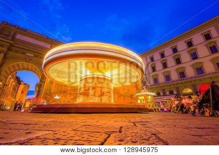 FLORENCE, ITALY - JUNE 12, 2015: Carousel at night iluminated in the middle of the square in Florence. Unidentified tourists waitting around.