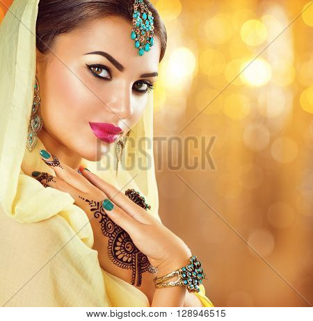 Beautiful fashion Indian woman portrait with oriental accessories- earrings, bracelets and rings. Arabic girl with black henna tattoos and beauty jewels. Hindu model with perfect make-up. India