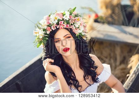 Portrait of young sexy woman on boat at sunset. The girl has a flower wreath on her head, relaxing and seiling on river. Fantasy art photography. Concept of female beauty, rest in the nature, and travel by water