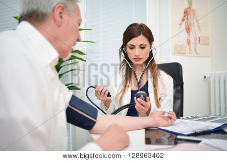 Doctor using a stethoscope and a sphygmomanometer to chec blood pressure