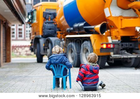 Two little kid boys having fun with looking on concrete mixer on construction and bulding own house for family.