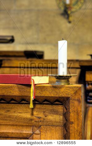Detail of hymnal and candle in church