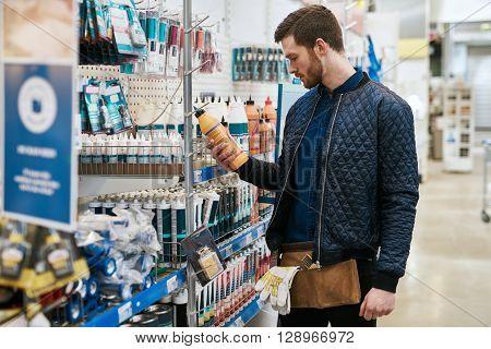 Handyman Selecting A Product At A Hardware Store