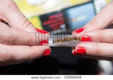 Close-up of woman holding rolling paperslim filter and tobacco