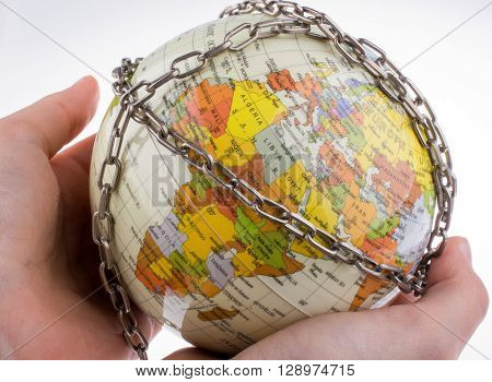 Hand holding a model globe in chains