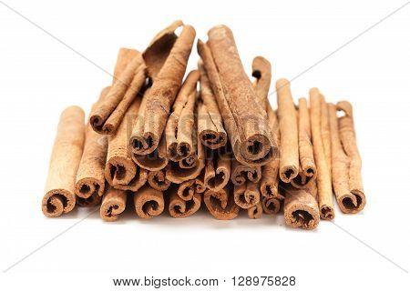 Top front Pile of Raw Organic Cinnamon sticks (Cinnamomum verum) isolated on white background.