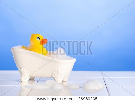 Rubber duck in the bath with soap suds on a blue background