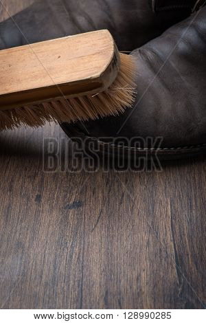 Old Worn Out Brown Leather Shoes With Brush Over The Dark Background